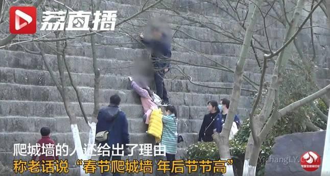 游客为讨彩头爬城墙